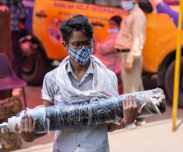 Symbolbild: Niedergeschlagener junger Mann mit leerer Sauerstoffflasche, Indien steht vor einem Engpass an medizinischem Sauerstoff